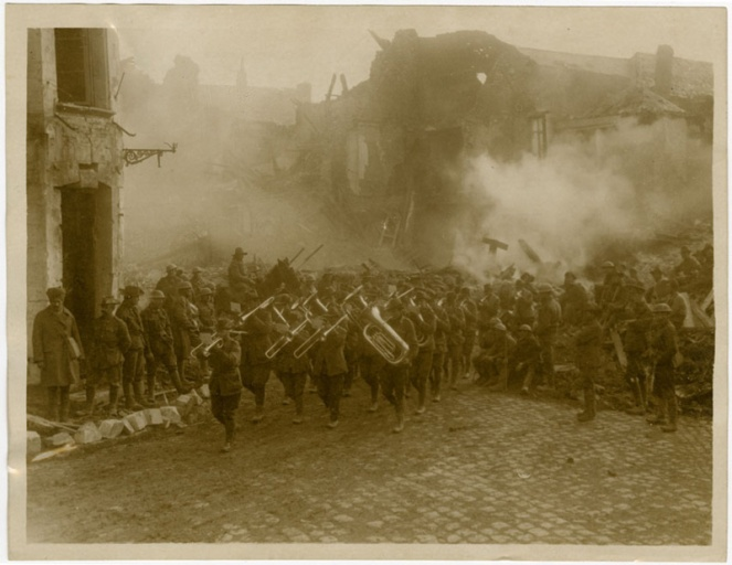 Australian band marching through a burning Bapaume street, 3 May 1917