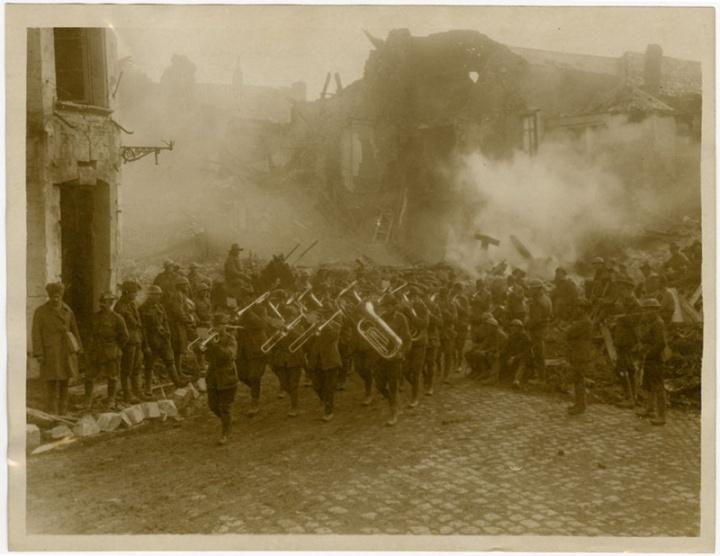 Australian band marching through a burning Bapaume street, 3 May 1917