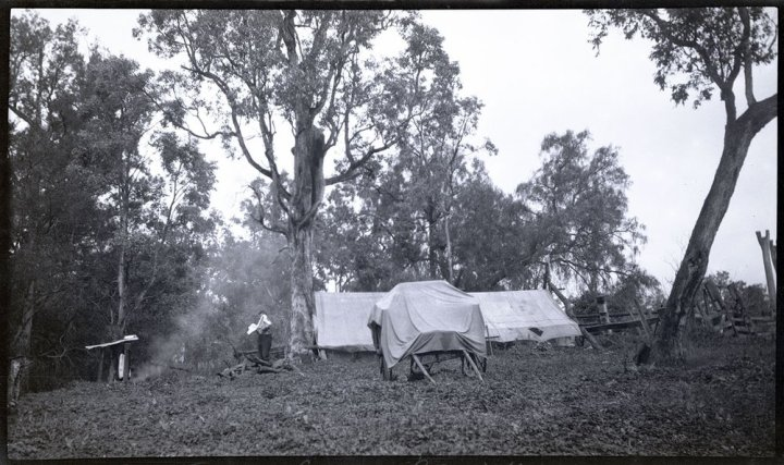 Mt Turners camp, Boyneside. Large tent, cover over wagon, man drying his face and burning fire c. 1920